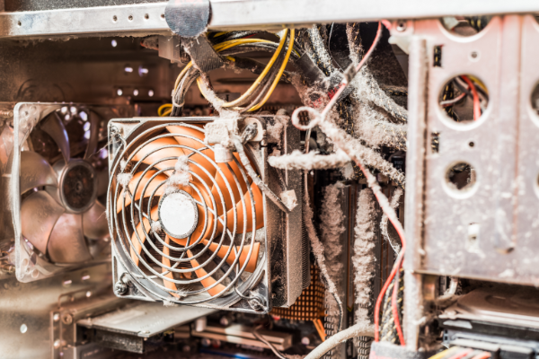 A photo showing the dirty inside of a computer with a fan