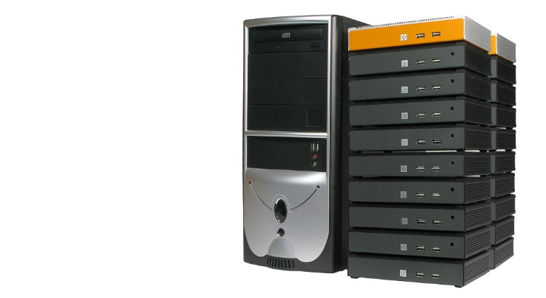 One large tower computer next to a stack of small low-profile industrial computers